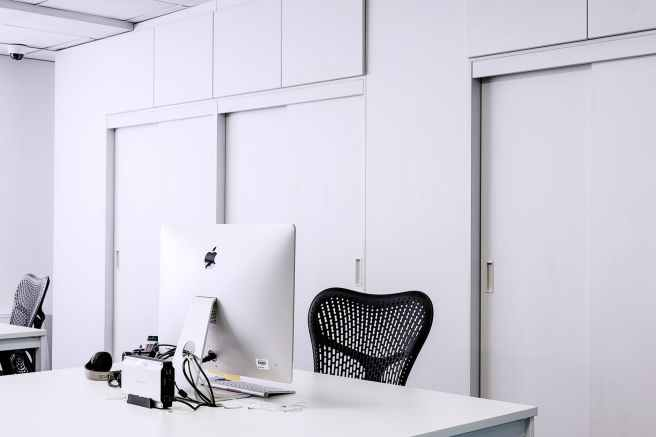 black mesh office rolling chair beside white wooden desk with white imac